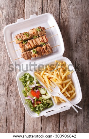 Fast food: kebabs, fries and fresh salad in the tray on the table. vertical top view