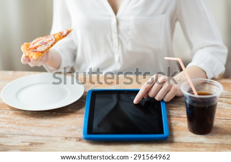 fast food, people, technology and diet concept - close up of woman hands with tablet pc computer, pizza and cola counting calories at table - stock photo