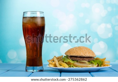 Fast food set of a burger, french fries and cola on blue background - stock photo