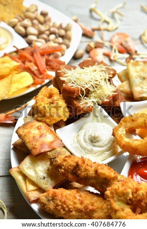 Fast food snacks composition with text copy pistachios nuts dried salty fish strips and croutons with cheese chicken nuggets on rustic wood background. Unhealthy junk food - stock photo