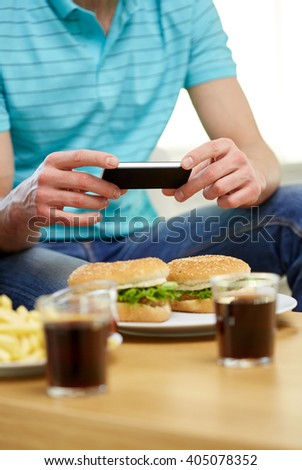 fast food, unhealthy eating, technology, people and junk-food - close up of man with smartphone photographing hamburgers at home