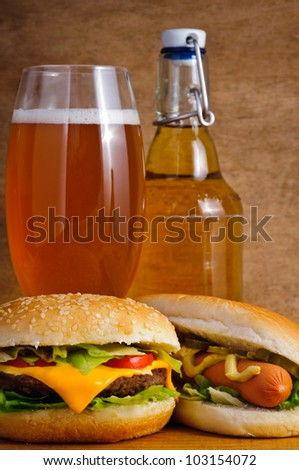 Fast food with cheeseburger, hot dog and beer - stock photo