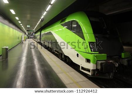 Fast green passenger commuter train puts on rails in empty subway. - stock photo