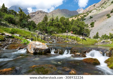 Fast mountain creek. Rapid water stream of river on foreground and group of people hiker walking up hill footpath on background - stock photo
