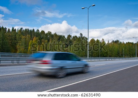 Fast moving car on highway - stock photo