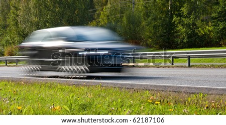 Fast moving modern car with led lights on highway - stock photo