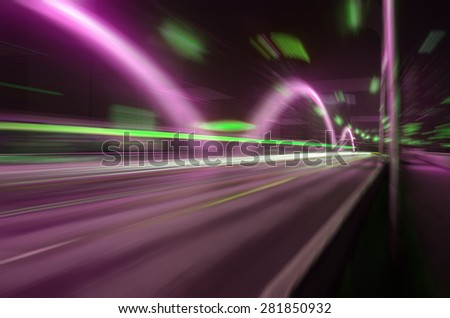 Fast-moving traffic on the bridge at night - stock photo