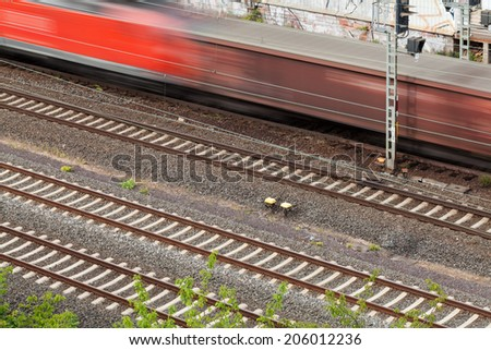 Fast moving train with red stripe passing by - stock photo