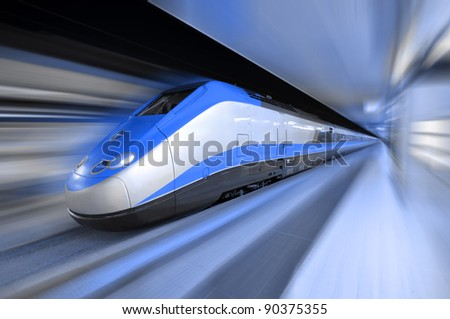 fast train traveling at high speed through a station - stock photo