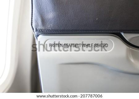 fasten seatbelt while seated - stock photo