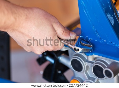 Fastening the screws on a small machine - closeup on hand - stock photo