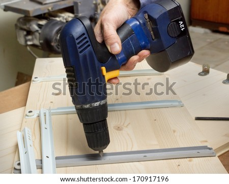 Fastening with an electric screwdriver furniture wooden parts in production of furniture