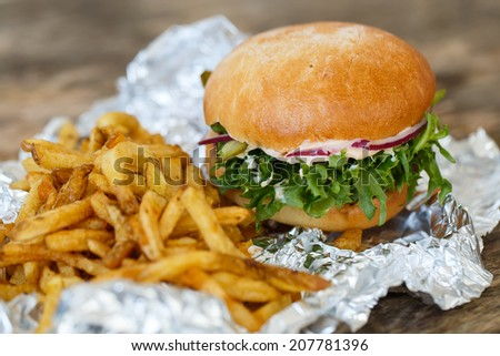 Fastfood, unhealthy. Tasty burger with fries on the table - stock photo