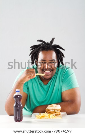 fat african american man eating chips - stock photo