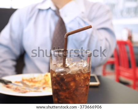Fat and unhealthy businessman having soft drink and junk food (focus on soft drink, blurred out the rest) - unhealthy and junk food concept - stock photo
