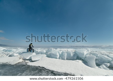Fat bike (also called fat bike or fat-tire bike) - Cycling on large wheels. A cyclist sits on the bike on the ice.