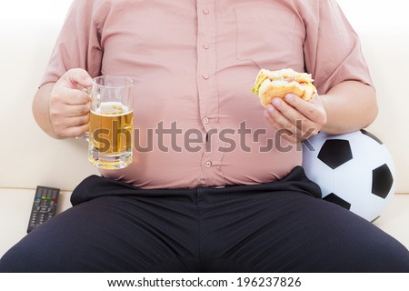 fat business man eating food and beer and sitting on sofa - stock photo