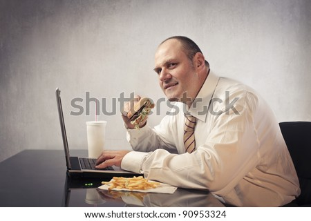 Fat businessman at the office eating junk food - stock photo