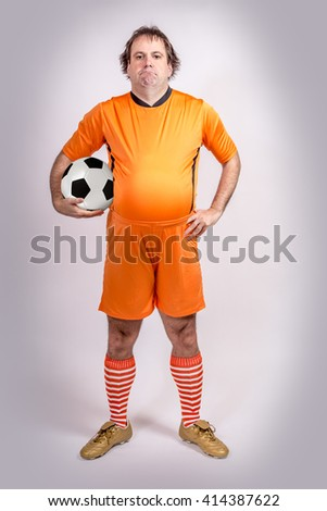 Fat football Soccer player with ball. Recreation footballer carries a ball. Proud fat football player carries the ball.