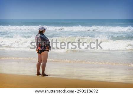 Fat lonely woman standing on the beach in Varkala, India - stock photo