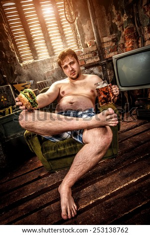 Fat man eating a hamburger sitting on a chair in the slums - stock photo