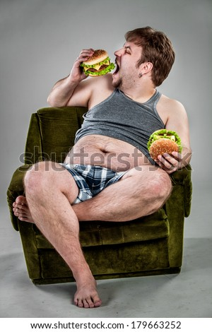 Fat man eating hamburger seated on armchair. Style fast food. - stock photo
