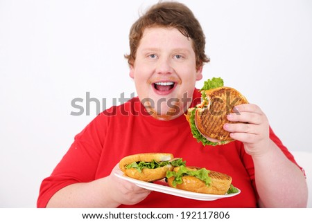 Fat man eating tasty sandwich on home interior background   - stock photo