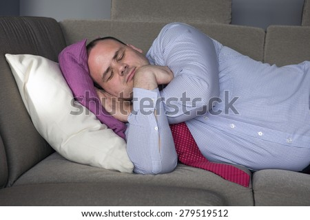 fat man in shirt and tie lying on couch and sleeps - stock photo