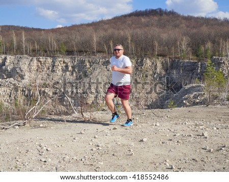 Fat man running in nature.An active holiday. Fitness, sports. Lifestyle. - stock photo