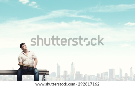 Fat man sitting on bench with book and looking away