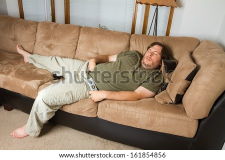 Fat man sleeping on the couch with his hand down his pants - stock photo
