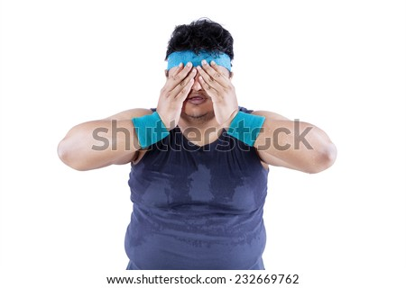 Fat man tired after workout and covering his face - stock photo