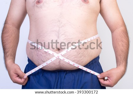 Fat man trying to measure waist circumference - stock photo