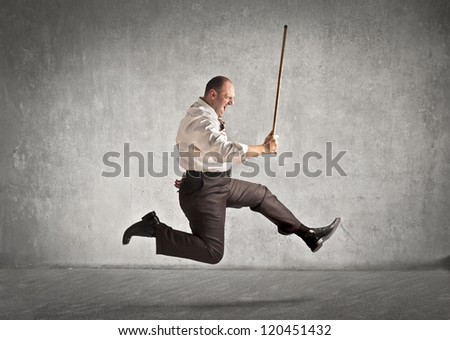 Fat man with a stick running after someone - stock photo