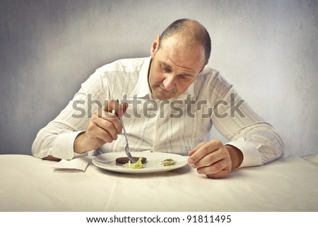 Fat man with doubtful expression examining the food in his dish - stock photo