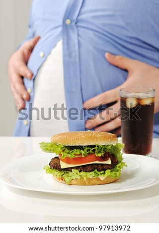 Fat man with hamburger and cola - stock photo