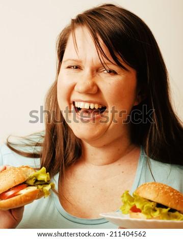 fat white woman having choice between hamburger and salad isolated - stock photo