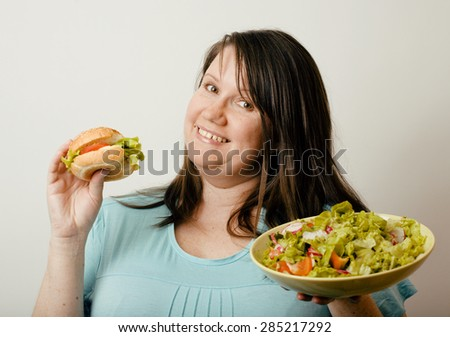 fat white woman having choice between hamburger and salad on white background