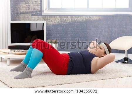 Fat woman doing gymnastics, abdominal exercises at home. - stock photo