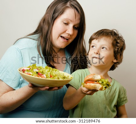 fat woman holding salad and little cute boy with hamburger teasing, real family on white