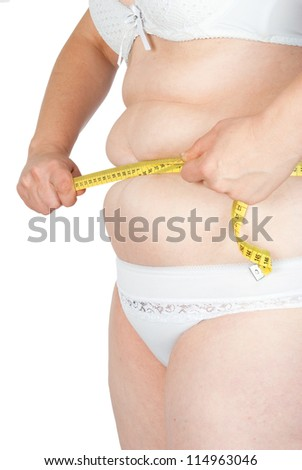 Fat woman measuring her stomach - stock photo