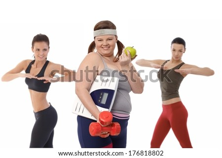 Fat woman on diet doing fitness exercise with slim sporty girls. - stock photo