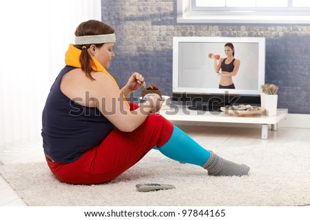 Fat woman sitting on floor with chocolate cake while watching fitness program on television. - stock photo