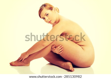 Fat woman sitting on the floor with knees close to chest