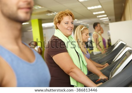 Fat woman training in gym, using running machine.