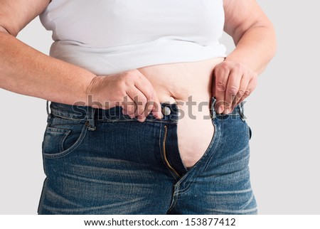 Fat woman trying to wear jeans. Isolated on grey background