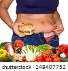 Fat woman with hamburger and vegetables - stock photo