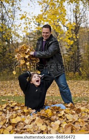 Father about to drop a handful of fall leaves on his daughter's head