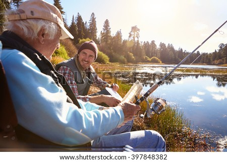 Father and adult son fishing lakeside, close-up - stock photo