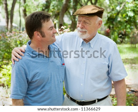 Father and adult son in the park together.  The father is proud of his son. - stock photo